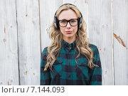 Купить «Serious blonde listening music with headphones», фото № 7144093, снято 2 октября 2014 г. (c) Wavebreak Media / Фотобанк Лори