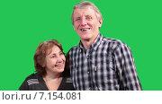 Довольная пожилая пара смеется, улыбается и целуется в камеру, зеленый изолированный фон. Стоковое видео, видеограф Кекяляйнен Андрей / Фотобанк Лори