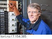 Купить «Электрик на производстве, пожилой мужчина», фото № 7154385, снято 22 декабря 2014 г. (c) Кекяляйнен Андрей / Фотобанк Лори