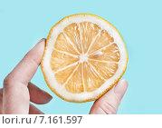 Ломтик лимона в пальцах, выдавливающих из него сок. Стоковое фото, фотограф Anna Alferova / Фотобанк Лори