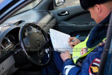 Сотрудник ГИБДД, сидя в машине, выписывает штраф за нарушение правил дорожного движения