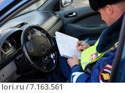 Купить «Сотрудник ГИБДД, сидя в машине, выписывает штраф за нарушение правил дорожного движения», эксклюзивное фото № 7163561, снято 20 марта 2015 г. (c) Яна Королёва / Фотобанк Лори