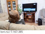 Купить «Женщина с телевизионным пультом управления на диване перед жк телевизором», фото № 7167385, снято 22 декабря 2014 г. (c) Кекяляйнен Андрей / Фотобанк Лори