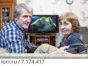 Купить «Пожилая пара сидит на диване перед телевизором и смотрит, обернувшись назад», фото № 7174417, снято 22 декабря 2014 г. (c) Кекяляйнен Андрей / Фотобанк Лори