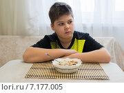 Купить «Подросток отказывается есть овсянку на завтрак», фото № 7177005, снято 26 марта 2015 г. (c) Володина Ольга / Фотобанк Лори
