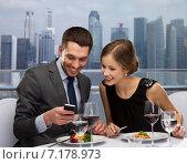 Купить «smiling couple with smartphone at restaurant», фото № 7178973, снято 9 марта 2014 г. (c) Syda Productions / Фотобанк Лори