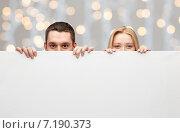 happy couple hiding behind big white blank board. Стоковое фото, фотограф Syda Productions / Фотобанк Лори