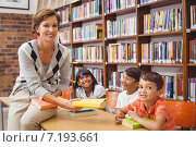 Купить «Cute pupils and teacher looking for books in library», фото № 7193661, снято 8 ноября 2014 г. (c) Wavebreak Media / Фотобанк Лори