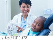 Купить «Dentist showing boy prosthesis teeth», фото № 7211273, снято 16 апреля 2014 г. (c) Wavebreak Media / Фотобанк Лори