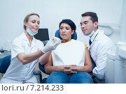 Купить «Dentists showing woman prosthesis teeth», фото № 7214233, снято 16 апреля 2014 г. (c) Wavebreak Media / Фотобанк Лори