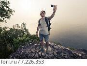 Купить «Турист делает селфи на вершине горы», фото № 7226353, снято 22 марта 2015 г. (c) Михаил Дударев / Фотобанк Лори