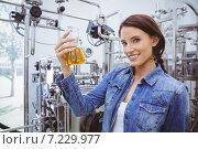 Купить «Smiling woman holding a beaker of beer», фото № 7229977, снято 30 июля 2014 г. (c) Wavebreak Media / Фотобанк Лори