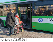 Купить «Мужчина помогает женщине в инвалидной коляске войти в автобус», эксклюзивное фото № 7250681, снято 11 апреля 2015 г. (c) Володина Ольга / Фотобанк Лори