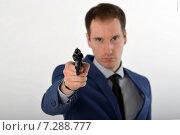 Купить «Мужчина в деловом костюме направил револьвер в сторону зрителя, револьвер в фокусе», фото № 7288777, снято 12 ноября 2019 г. (c) Ивашков Александр / Фотобанк Лори