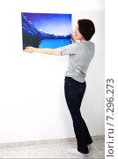 Купить «Девушка вешает картину», фото № 7296273, снято 9 апреля 2015 г. (c) Сергей Слозин / Фотобанк Лори