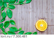 Листья шпината и апельсиновая долька на бамбуковом коврике. Стоковое фото, фотограф Петрова Инна / Фотобанк Лори