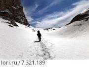 Купить «Турист идёт по снегу в горном ущелье», фото № 7321189, снято 1 мая 2013 г. (c) Анна Полторацкая / Фотобанк Лори