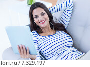 Купить «Smiling beautiful brunette relaxing on the couch and listening music», фото № 7329197, снято 14 октября 2014 г. (c) Wavebreak Media / Фотобанк Лори