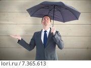 Купить «Composite image of businessman sheltering under black umbrella», фото № 7365613, снято 25 марта 2019 г. (c) Wavebreak Media / Фотобанк Лори