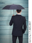 Купить «Composite image of rear view of businessman sheltering with umbrella», фото № 7365897, снято 25 марта 2019 г. (c) Wavebreak Media / Фотобанк Лори