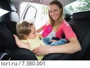 Mother securing her baby in the car seat. Стоковое фото, агентство Wavebreak Media / Фотобанк Лори