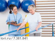 Therapist looking senior woman walking with parallel bars. Стоковое фото, агентство Wavebreak Media / Фотобанк Лори