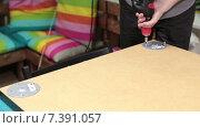 Мужчина собирает мебель с помощью электрической дрели. Стоковое видео, видеограф Кекяляйнен Андрей / Фотобанк Лори