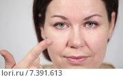Молодая женщина держит на пальце контактную глазную линзу, фокусировка на лице и руке. Стоковое видео, видеограф Кекяляйнен Андрей / Фотобанк Лори