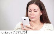 Купить «Веселая девушка листает страницы на экране телефона и пишет сообщения, серый фон», видеоролик № 7391761, снято 8 марта 2015 г. (c) Кекяляйнен Андрей / Фотобанк Лори