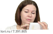 Купить «Красивая девушка пользуется мобильным телефоном и говорит в камеру, белый изолированный фон», видеоролик № 7391805, снято 5 марта 2015 г. (c) Кекяляйнен Андрей / Фотобанк Лори