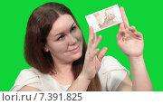 Купить «Довольная симпатичная женщина рассматривает купюру в сто рублей, зеленый изолированный фон», видеоролик № 7391825, снято 5 марта 2015 г. (c) Кекяляйнен Андрей / Фотобанк Лори
