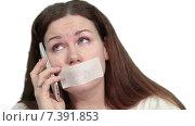 Купить «Женщина с заклеенным ртом пытается разговаривать по сотовому телефону, белый изолированный фон», видеоролик № 7391853, снято 4 марта 2015 г. (c) Кекяляйнен Андрей / Фотобанк Лори