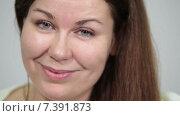 Красивая девушка с длинными волосами улыбается в камеру, крупный план. Стоковое видео, видеограф Кекяляйнен Андрей / Фотобанк Лори