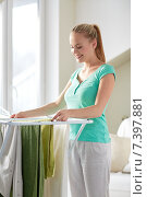 Купить «happy woman hanging clothes on dryer at home», фото № 7397881, снято 25 января 2015 г. (c) Syda Productions / Фотобанк Лори