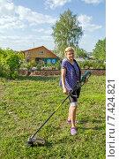 Женщина косит траву с помощью триммера. Стоковое фото, фотограф Евгений Ткачёв / Фотобанк Лори