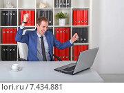 Купить «Молодой мужчина смотрит на экран ноутбука и радуется успеху на своем рабочем месте в офисе», фото № 7434881, снято 19 апреля 2015 г. (c) Ивашков Александр / Фотобанк Лори