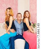 Любовный треугольник. Две девушки сидят на коленях счастливого молодого мужчины. Стоковое фото, фотограф Петр Малышев / Фотобанк Лори