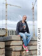 Купить «Молодой мужчина сидит на сложенных бетонных плитах на фоне башенных кранов», фото № 7453441, снято 16 мая 2015 г. (c) Ивашков Александр / Фотобанк Лори
