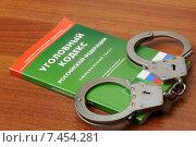 Купить «Наручники лежат на уголовном кодексе Российской Федерации», фото № 7454281, снято 30 апреля 2015 г. (c) Денис Ларкин / Фотобанк Лори