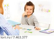 Купить «Дошкольник. Веселый мальчик сидит за столом перед карточками, которые разложены на столе», фото № 7463377, снято 15 марта 2015 г. (c) Сергей Новиков / Фотобанк Лори
