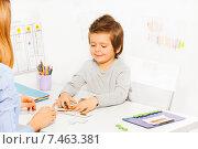 Купить «Мальчик сидит перед взрослым за столом в детском саду и собирает пазл», фото № 7463381, снято 15 марта 2015 г. (c) Сергей Новиков / Фотобанк Лори