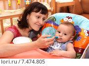 Купить «Молодая мама кормит ребенка в кресле», фото № 7474805, снято 17 октября 2014 г. (c) Виктор Топорков / Фотобанк Лори