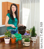 Happy woman transplanting flowers plant. Стоковое фото, фотограф Яков Филимонов / Фотобанк Лори