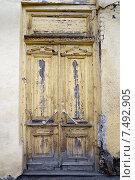 Купить «Старая деревянная входная дверь с облупившейся краской», фото № 7492905, снято 27 февраля 2015 г. (c) Юлия Батурина / Фотобанк Лори