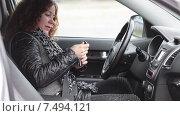 Купить «Молодая женщина водитель ищет ключи зажигания, сидя в салоне автомобиля», видеоролик № 7494121, снято 5 мая 2015 г. (c) Кекяляйнен Андрей / Фотобанк Лори