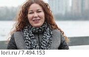 Женщина с кудрявыми волосами смотрит в камеру и говорит на улице на ветру. Стоковое видео, видеограф Кекяляйнен Андрей / Фотобанк Лори