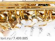 Купить «Блестящий золотой саксофон лежит на нотных листах», фото № 7499885, снято 23 февраля 2015 г. (c) Сергей Новиков / Фотобанк Лори