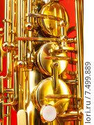 Купить «Крупным планом вид саксофона на красном фоне», фото № 7499889, снято 23 февраля 2015 г. (c) Сергей Новиков / Фотобанк Лори