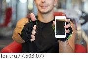 Купить «young man with smartphone showing thumbs up in gym», фото № 7503077, снято 28 сентября 2014 г. (c) Syda Productions / Фотобанк Лори