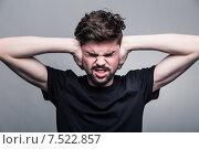 Купить «Мне нужна тишина. Молодой человек в футболке закрывает уши руками», фото № 7522857, снято 30 апреля 2015 г. (c) Константин Колосов / Фотобанк Лори